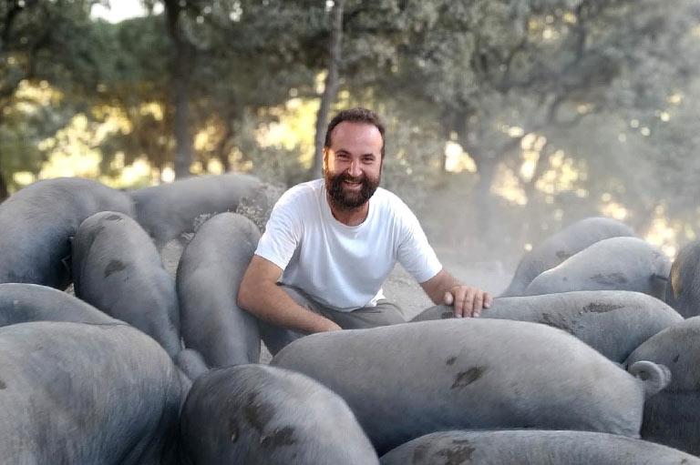 Productor de jamón ecológico Antonio Marin, rodeado de cerdos de raza ibérica